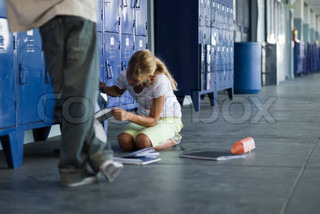 Junior high student picking up dropped school supplies, boy standing by watching