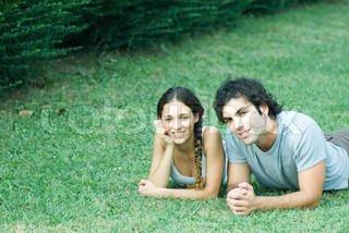 Couple lying on grass, side by side, smiling at camera