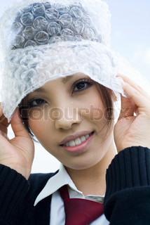 Young female wearing hat made of bubble wrap, portrait