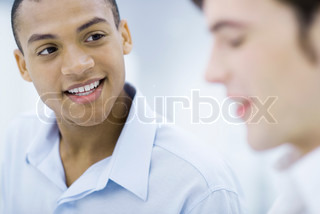Young professional man chatting with colleague, smiling