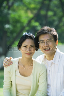 Couple smiling at camera, man with arm around woman