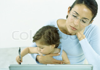 Woman with eyes closed holding little girl drawing with pen