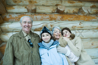 Senior couple standing with teen and preteen granddaughters in front of log cabin, smiling, portrait