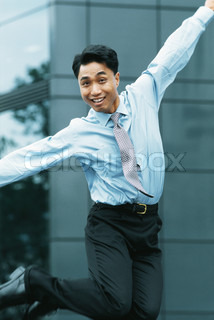Businessman jumping in the air, arms out, smiling at camera