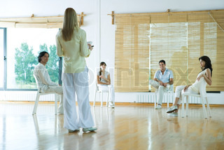 Woman leading group therapy session, rear view