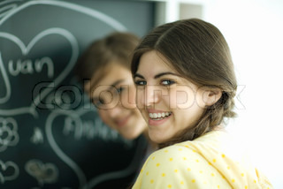 Two young female friends standing at chalkboard, smiling at camera