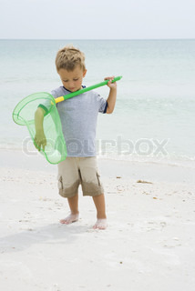 Young boy standing at the beach, reaching for ball in net