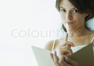 Young woman with pen to lips, holding notebook