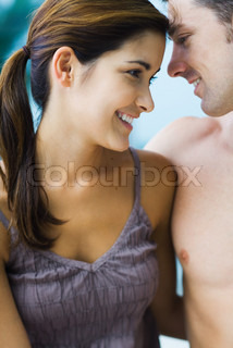 Couple with heads close together, smiling, cropped view, close-up