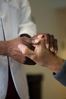 Læge holder patientens hånd