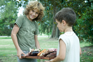 Two boys holding tray of grilled meats