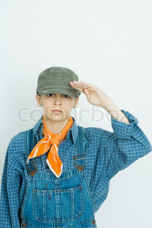 Teenage girl dressed in overalls and hat, saluting camera, portrait
