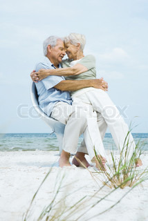Senior couple sitting in chair together on beach with foreheads touching, woman sitting on man's lap