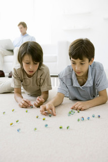 Boys lying on the floor playing with marbles, father sitting on sofa with laptop in background