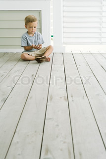 Boy sitting on the ground next to bird's nest, looking down at eggs in his hands