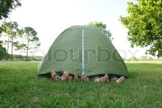 Young friends in tent, feet sticking out