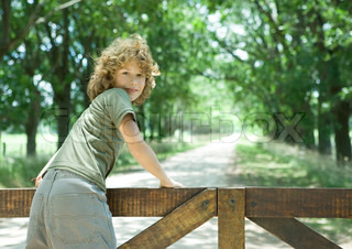 Boy leaning against wooden fence, looking over shoulder at camera