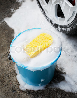 Bucket with soapy water, a sponge and a car wheel.