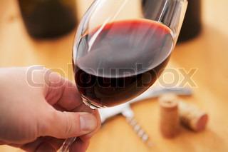 En hånd, der holder et glas rødvin mens du ser på farven på vinen