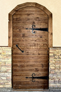 Brown wooden door with black metal handles and hinges on a beige background of whitewashed walls and decorative wooden