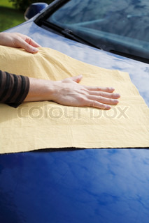 Hands drying a blue car with synthetic chamois leather