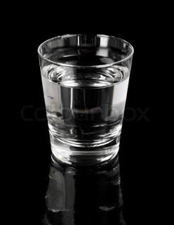 Et glas vand på sort reflekterende overflade