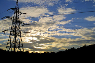 Sun settings behind electricity pylon