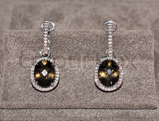 Elegant jewelry earrings with topaz and brilliants over textile background