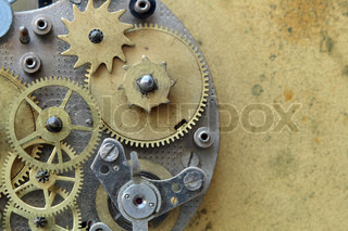 Closeup of old metal clock mechanism on yellow brass background