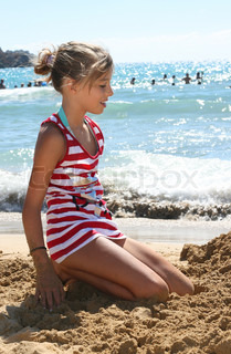 A smiling young girl on the sand near the sea