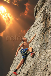 A guy climbs on a rock against the sky with a sunset
