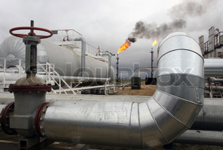 Set of pipes of oil factory against a flame