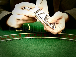 Men's hands shuffle a deck of cards at a casino table