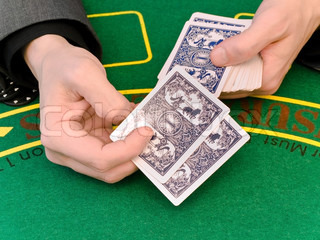 the hands of men sit playing cards at a table in a casino