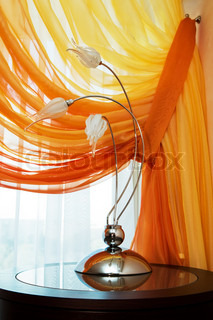 Modern lamp on a background of an orange curtain