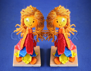 Doll with blond hair on blue background