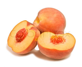 whole and cut peaches on a white background