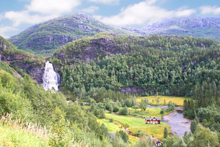 Landscape with a waterfall and houses in the Norwegian mountains