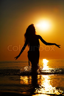 Silhouette of a girl in the water at sunset. Natural light and dark. Artistic colors added. Horizontal photo