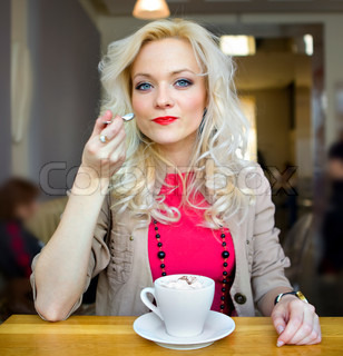 young blonde in cafe at little table with cup of coffee