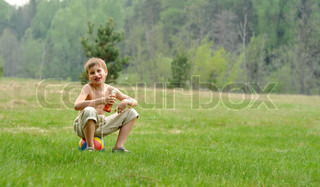 little boy with a colour ball sitting on the gass