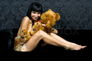 Beautiful girl is playing with teddy bear. Fun