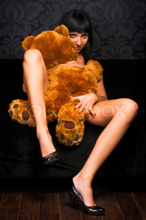 Beautiful naked girl is holding a teddy bear on her knees