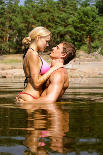 Young beautiful  couple are kissing in the water