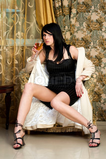 Portrait of the beautiful woman. She is drinking wine in the bar