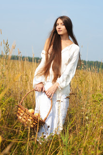 Summer field. Portrait of the beautiful woman with busket