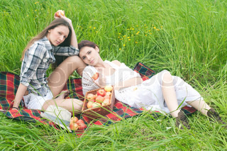 Two beautiful women are relaxing on the meadow