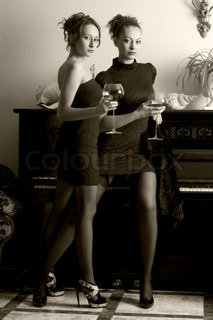 Two beautiful women are drinking wine in the luxurious interiors. Monochrome image