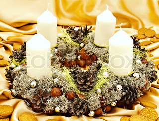 Christmas handmade garland with candles, cookie and natural decorations at golden textile