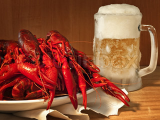 red boiled crawfishes on plate and beer
